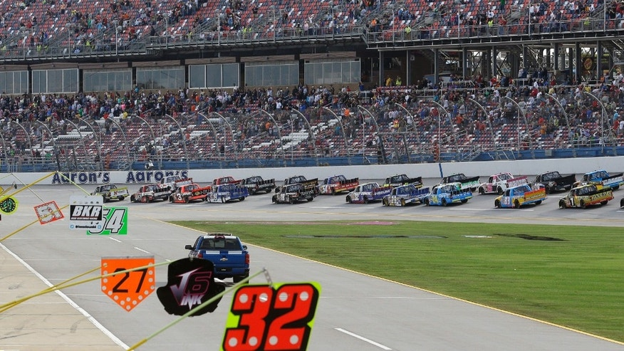 Trucks race through the tri-oval at the start of the NASCAR Camping World Truck Series race at Talladega Superspeedway in Talladega, Ala., Saturday, Oct. 19, 2013. (AP Photo/Dave Martin)
