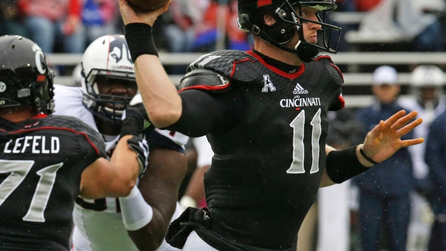 Cincinnati quarterback Brendon Kay (11) passes against Connecticut in the first half of an NCAA college football game, Saturday, Oct. 19, 2013, in Cincinnati. (AP Photo/Al Behrman)