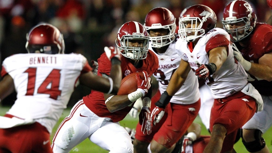 Alabama running back Kenyan Drake (17) cuts between Arkansas safety Eric Bennett (14) and Arkansas linebacker Jarrett Lake (39) for a first down run during the first half of an NCAA college football game on Saturday, Oct. 19, 2013, in Tuscaloosa, Ala. (AP Photo/Butch Dill)