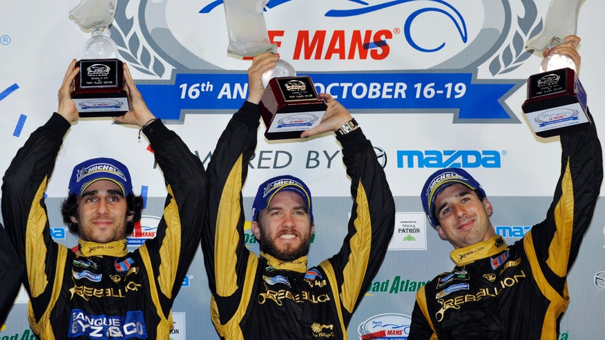 From left, Nicolas Prost, of France&#x3b; Nick Heidfeld, of Germany&#x3b; and Neel Jani, of Switzerland, celebrate on the podium after taking the overall win at the American Le Mans Series' Petit Le Mans auto race at Road Atlanta, Saturday, Oct. 19, 2013, in Braselton, Ga. (AP Photo/Rainier Ehrhardt)
