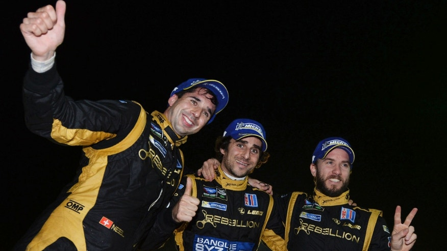 From left, Neel Jani, of Switzerland; Nicolas Prost, of France; and Nick Heidfeld, of Germany, celebrate taking the overall win at the American Le Mans Series' Petit Le Mans auto race at Road Atlanta, Saturday, Oct. 19, 2013, in Braselton, Ga. (AP Photo/Rainier Ehrhardt)