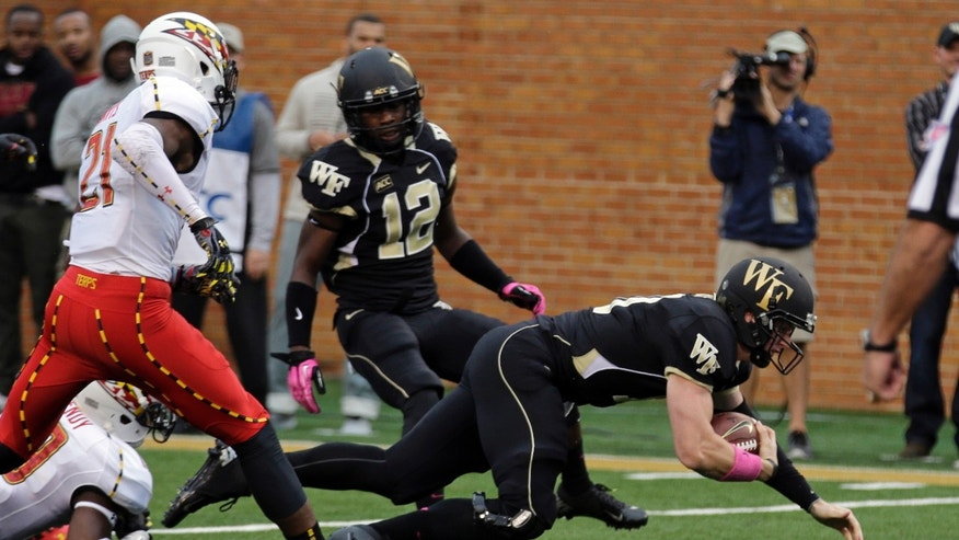 Wake Forest's Tanner Price, right, dives to the goal line for a touchdown as Maryland's Sean Davis, left, defends in the first half of an NCAA college football game in Winston-Salem, N.C., Saturday, Oct. 19, 2013. (AP Photo/Chuck Burton)