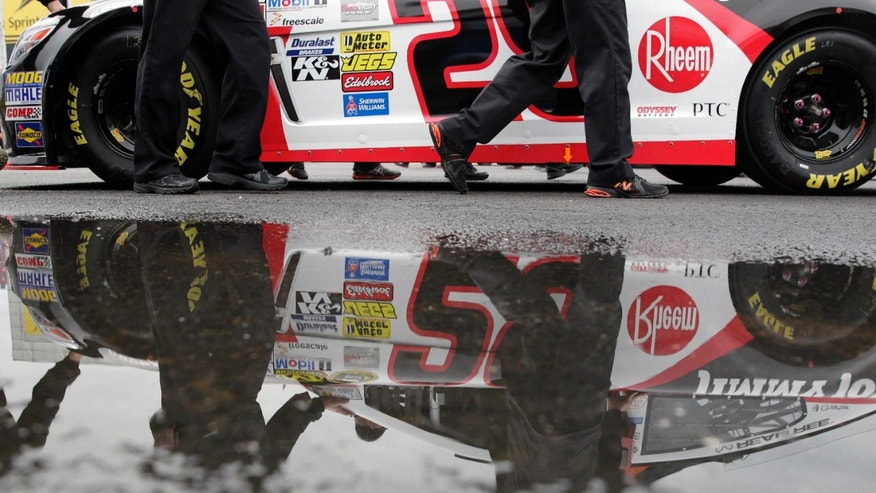 Pit crew members push the car of Kevin Harvick back to the garage after rain forced the cancellation for Sunday's NASCAR Sprint Cup Series auto race at Talladega Superspeedway in Talladega, Ala., Saturday, Oct. 19, 2013. Drivers will start based on their practice times on Friday. (AP Photo/Jay Sailors)