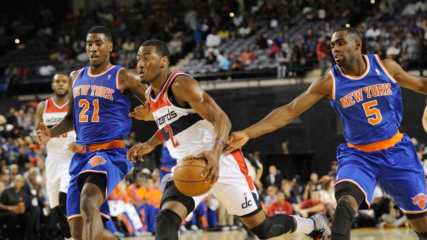 Washington Wizards guard John Wall (2) drives up court against New York Knicks guard Iman Shumpert (21) and Tim Hardaway Jr. (5) during the first half of an NBA preseason basketball game, Thursday, Oct. 17, 2013, in Baltimore. (AP Photo/Nick Wass)