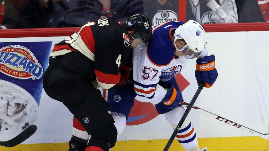 Ottawa Senators' Chris Phillips (4) and Edmonton Oilers' David Perron (57) fight for possession of the puck during the second period of an NHL hockey in Ottawa, Saturday, Oct. 19, 2013. (AP Photo/The Canadian Press, Fred Chartrand)