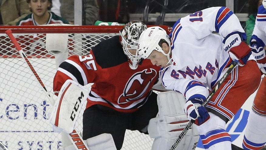 New Jersey Devils golie Cory Schneider, left, defends against New York Rangers center Brad Richards (19) during the second period of an NHL hockey game, Saturday, Oct. 19, 2013, in Newark, N.J. (AP Photo/Julio Cortez)