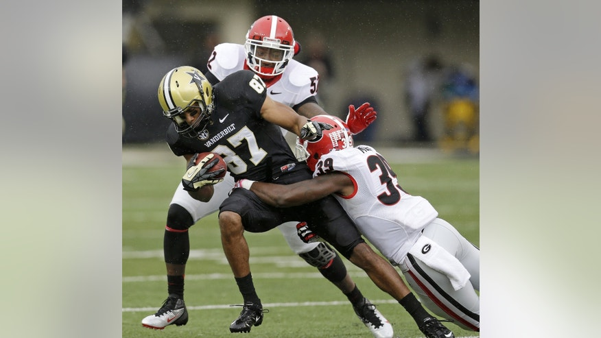 Vanderbilt wide receiver Jordan Matthews (87) is stopped by Georgia defenders Corey Moore (39) and Amarlo Herrera (52) in the first quarter of an NCAA college football game on Saturday, Oct. 19, 2013, in Nashville, Tenn. (AP Photo/Mark Humphrey)
