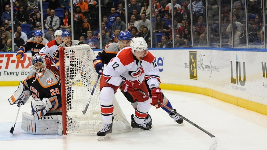 Carolina Hurricanes' Eric Staal (12) chases down the puck as New York Islanders' Brian Strait and goalie Evgeni Nabokov (20) defend during the first period of an NHL hockey game Saturday, Oct. 19, 2013, in Uniondale, N.Y. (AP Photo/Kathy Kmonicek)