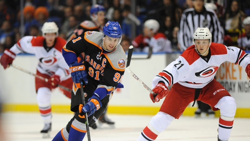 New York Islanders' John Tavares (91) drives the puck down ice away from Carolina Hurricanes' Drayson Bowman (21) Carolina Hurricanes in the second period of an NHL hockey game Saturday, Oct. 19, 2013, in Uniondale, N.Y. (AP Photo/Kathy Kmonicek)