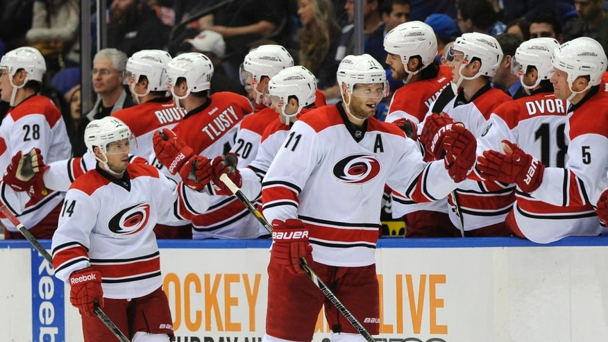 Carolina Hurricanes' Jordan Staal (11) and Nathan Gerbe (14) celebrate Staal's goal against the New York Islanders with teammates in the second period of an NHL hockey game Saturday, Oct. 19, 2013, in Uniondale, N.Y. (AP Photo/Kathy Kmonicek)