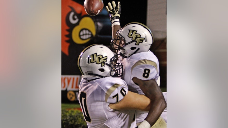 Central Florida running back Storm Johnson (8) celebrates with lineman Chris Martin (70) after scoring a touchdown against Louisville in the third quarter of an NCAA college football game in Louisville, Ky., Friday, Oct. 18, 2013. UCF came back to upset Louisville, 38-35. (AP Photo/Garry Jones)