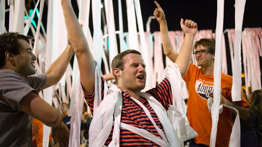 "Brad Penter, Auburn senior, throws both his hands up and yells ""war eagle"" on Saturday, Oct. 19, 2013, at Toomer's Corner in Auburn, Ala. The ""rolling of Toomer's Corner"" came after Auburn defeated Texas A&M 45-41. (AP Photo/Opelika-Auburn News, Albert Cesare)"