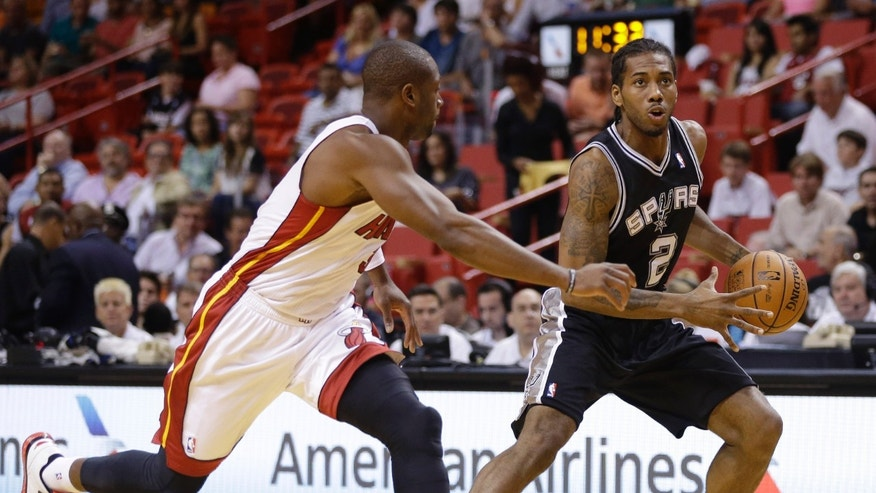 San Antonio Spurs' Kawhi Leonard (2) drives to the basket as Miami Heat's Dwyane Wade, left, defends during the first half of an NBA preseason basketball game, Saturday, Oct. 19, 2013, in Miami. (AP Photo/Lynne Sladky)