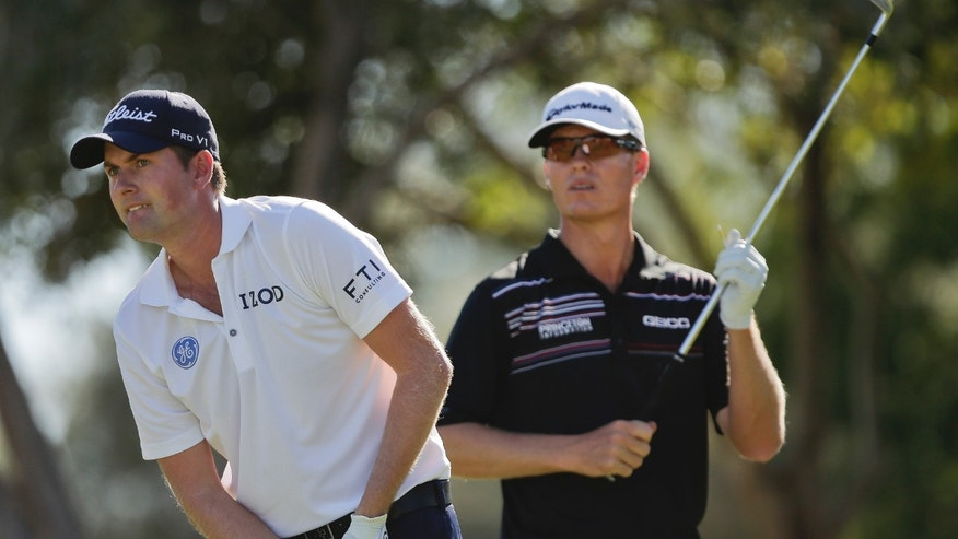 Webb Simpson, left, watches his tee shot off the eighth hole with John Senden in the third round of the Shriners Hospitals for Children Open golf tournament, Saturday, Oct. 19, 2013, in Las Vegas. (AP Photo/Julie Jacobson)