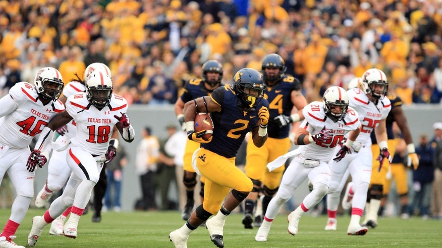 West Virginia's Dreamius Smith (2) runs past several Texas Tech defenders for a touchdown during the second quarter of their NCAA college football game in Morgantown, W.Va., on Saturday, Oct. 19, 2013. (AP Photo/Christopher Jackson)