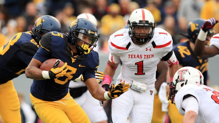 West Virginia's Charles Sims (3) carries the ball as Texas Tech's Tanner Jacobson (20) prepares for a tackle during their NCAA college football game in Morgantown, W.Va., on Saturday, Oct. 19, 2013. Texas Tech won 37-27. (AP Photo/Chris Jackson)