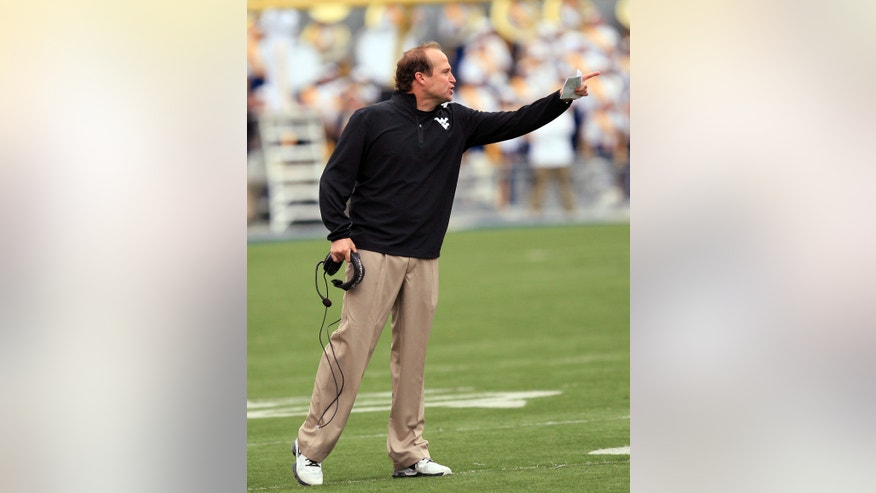 West Virginia coach Dana Holgorsen yells at an official during the third quarter of an NCAA college football game against Texas Tech in Morgantown, W.Va., on Saturday, Oct. 19, 2013. Texas Tech won 37-27. (AP Photo/Chris Jackson)