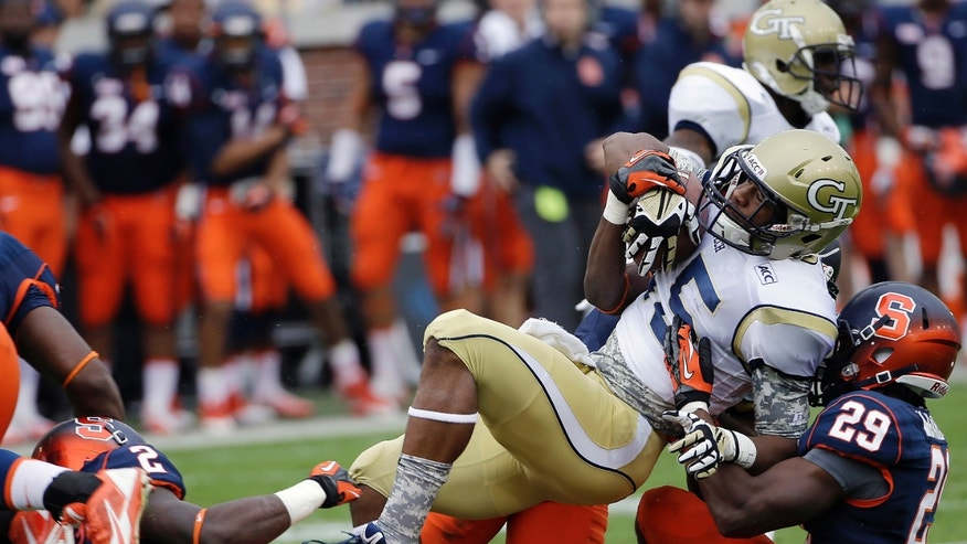 Georgia Tech wide receiver DeAndre Smelter (15) is brought down by Syracuse defenders during a punt return in the first half of an NCAA college football game Saturday, Oct. 19, 2013, in Atlanta. (AP Photo/John Bazemore)