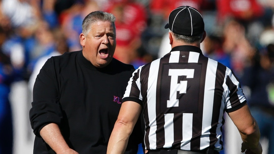 Kansas coach Charlie Weis, left, talks with field judge J. Taylor following a penalty during the first half of an NCAA college football game against Oklahoma in Lawrence, Kan., Saturday, Oct. 19, 2013. (AP Photo/Orlin Wagner)