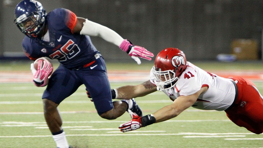 Arizona's Ka'Deem Carey (25) tries to out run the reach of Utah's Jared Norris (41) in the first half of an NCAA college football game, Saturday, Oct. 19, 2013 in Tucson, Ariz.  (AP Photo/Wily Low)