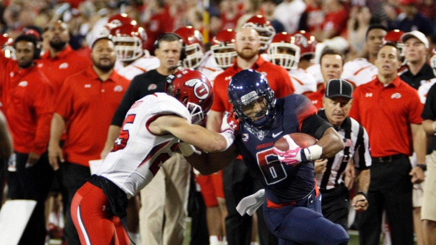Arizona's Nate Phillips (6) tries to stiff arm Utah's Mike Honeycutt (25)in the first half of an NCAA college football game, Saturday, Oct. 19, 2013 in Tucson, Ariz.  (AP Photo/Wily Low)