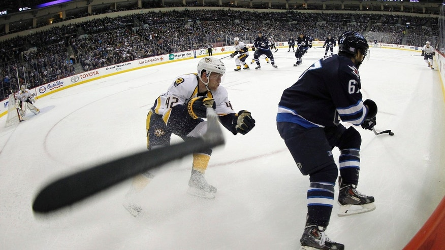 Nashville Predators' Mattias Ekholm (42) tries to check Winnipeg Jets' Michael Frolik (67) into the boards during second period NHL hockey action in Winnipeg, Manitoba, Sunday, Oct. 20, 2013.  (AP Photo/The Canadian Press, Trevor Hagan)