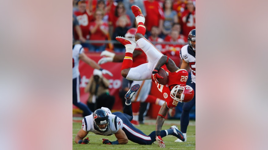 Kansas City Chiefs wide receiver Dwayne Bowe (82) is knocked down by Houston Texans free safety Shiloh Keo (31) during the first half of an NFL football game at Arrowhead Stadium in Kansas City, Mo., Sunday, Oct. 20, 2013. (AP Photo/Ed Zurga)