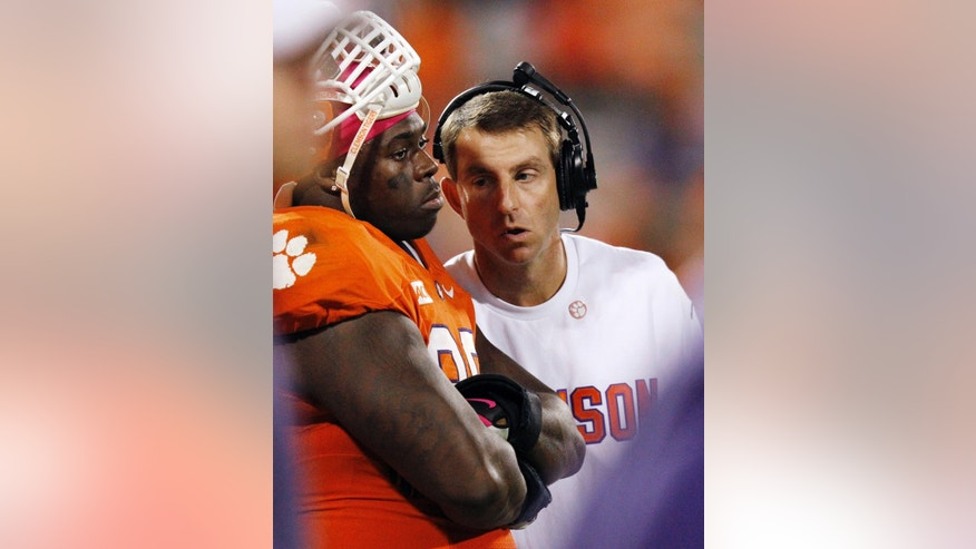 Clemson coach Dabo Swinney speaks to defensive tackle DeShawn Williams (99) in the closing minutes of an NCAA college football game, Saturday, Oct. 19, 2013, in Clemson, S.C. Florida State won 51-14. (AP Photo/Mike Stewart)