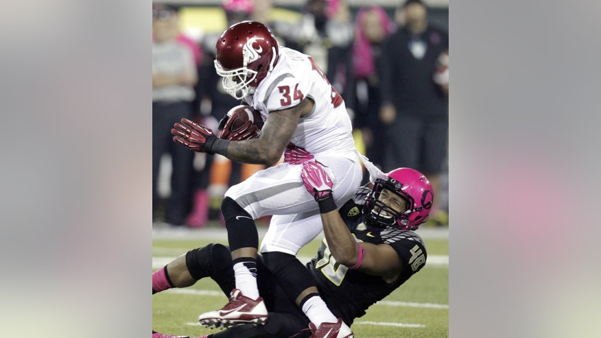 Oregon defender Rodney Hardick, right, pulls down Washington State running back Teondray Caldwell during the second half of an NCAA college football game in Eugene, Ore., Saturday, Oct. 19, 2013. Oregon won 62-38.(AP Photo/Don Ryan)
