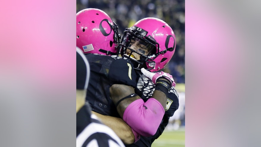 Oregon quarterback Marcus Mariota, right, hugs teammate Josh Huff after Huff scored on a pass from Mariota during the second half of an NCAA college football game against Washington State in Eugene, Ore., Saturday, Oct. 19, 2013.  Oregon won 62-38.(AP Photo/Don Ryan)