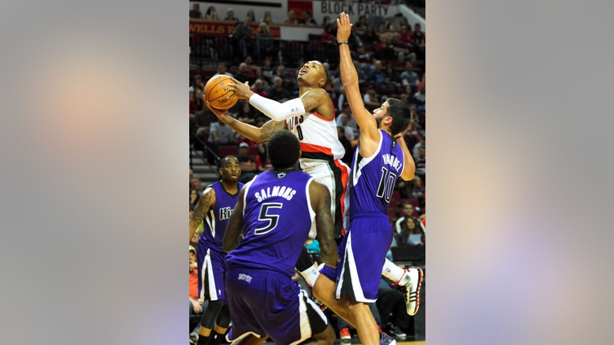 Portland Trail Blazers guard Damian Lillard (0) drives to the basket on Sacramento Kings guard Greivis Vasquez (10) during the first half of an NBA basketball game Sunday, Oct. 20, 2013, in Milwaukee. (AP Photo/Steve Dykes)