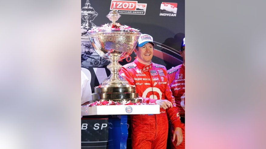 Scott Dixon, of New Zealand, stands with the trophy for winning the IndyCar Series Championship after finishing fifth in the Indy Car auto race at the Auto Club Speedway, Saturday, Oct. 19, 2013, in Fontana, Calif. (AP Photo/Alex Gallardo)