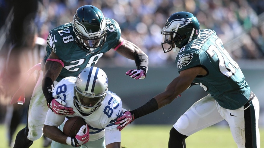 Dallas Cowboys wide receiver Terrance Williams (83) is brought down by Philadelphia Eagles free safety Earl Wolff (28) and cornerback Cary Williams during the first half of an NFL football game Sunday, Oct. 20, 2013, in Philadelphia. (AP Photo/Michael Perez)