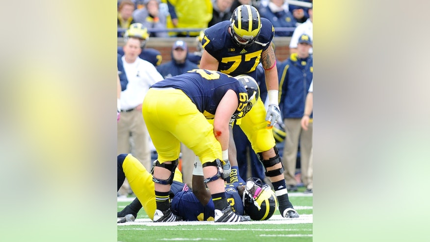 Michigan quarterback Devin Gardner, bottom, gets helped up off the field by offensive lineman Kyle Bosch, left, and Taylor Lewan (77), after being hit by an Indiana lineman while throwing a pass out of bounds and being called for intentional grounding during the second quarter of an NCAA football game at Michigan Stadium in Ann Arbor, Saturday, Oct. 19, 2013. (AP Photo/Lon Horwedel)