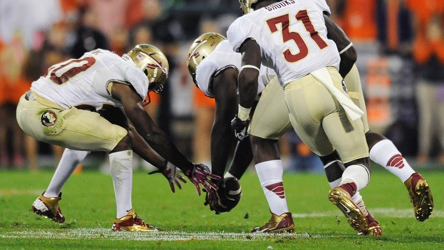 Florida State defensive end Mario Edwards Jr., center, picks up a fumbled ball as defensive backs Lamarcus Joyner, left, and Terrence Brooks (31) watch during the first half of an NCAA college football game against Clemson, Saturday, Oct. 19, 2013, in Clemson, S.C. (AP Photo/Richard Shiro)