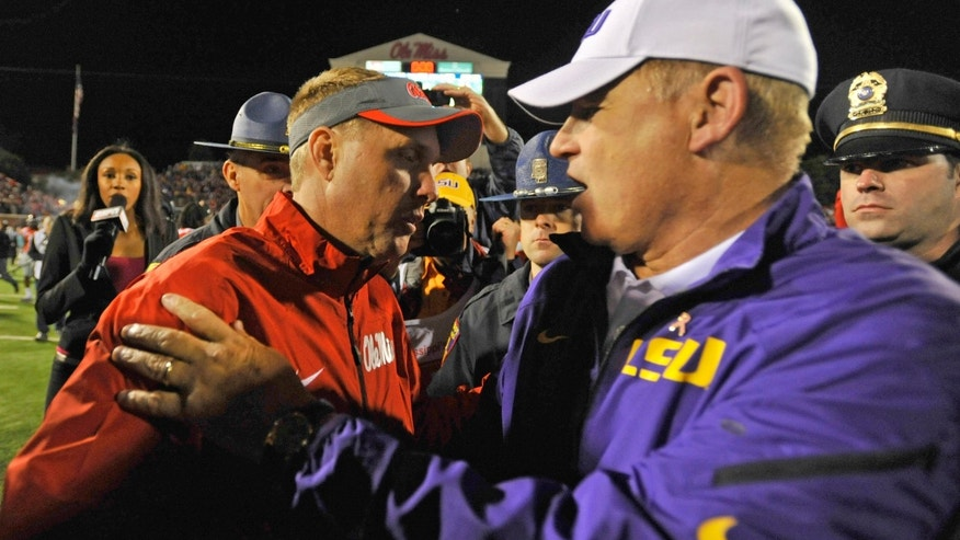 Mississippi coach Hugh Freeze (left) meets LSU coach Les Miles (right) at the end of an NCAA college football game on Saturday, Oct. 19, 2013, in Oxford, MS. Mississippi won 27-24. (AP Photo/ The Daily Mississippian, Austin McAfee)