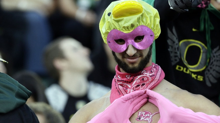 An Oregon fan sporting pink colors poses  for the camera in the stands before an NCAA college football game against Washington State in Eugene, Ore., Saturday, Oct. 19, 2013. (AP Photo/Don Ryan)
