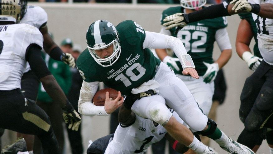 Michigan State quarterback Connor Cook, top, is stopped on a keeper by Purdue's Normondo Harris during the fourth quarter of an NCAA college football game, Saturday, Oct. 19, 2013, in East Lansing, Mich. Michigan State won 14-0. (AP Photo/Al Goldis)