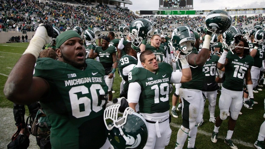 Michigan State players, including Micajah Reynolds (60), Danny Folino (19) and Trae Waynes (15), sing the school fight song as they celebrate their 14-0 win over Purdue in an NCAA college football game, Saturday, Oct. 19, 2013, in East Lansing, Mich. (AP Photo/Al Goldis)