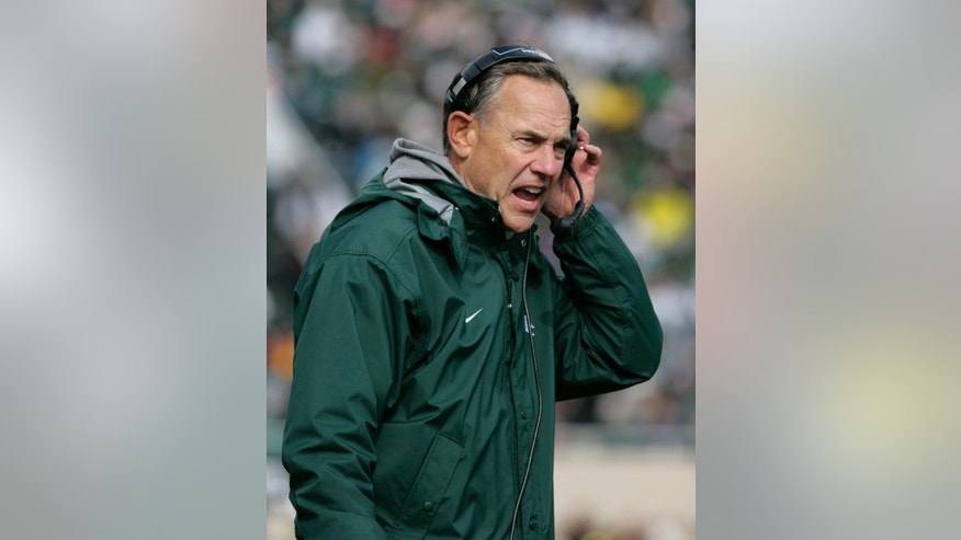 Michigan State coach Mark Dantonio shouts into his headset on the sidelines during the third quarter of an NCAA college football game against Purdue, Saturday, Oct. 19, 2013, in East Lansing, Mich. Michigan State won 14-0. (AP Photo/Al Goldis)