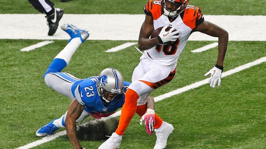 Cincinnati Bengals wide receiver A.J. Green (18) breaks the tackle of Detroit Lions cornerback Chris Houston (23) on an 82-yard touchdown reception in the first quarter of an NFL football game  Sunday, Oct. 20, 2013, in Detroit. (AP Photo/Paul Sancya)