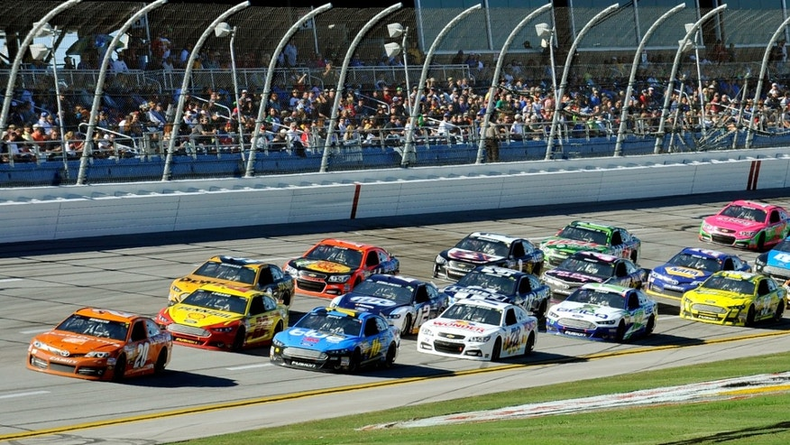Sprint Cup Series driver Matt Kenseth (20) leads a pack of cars through the tri-oval during the NASCAR Sprint Cup Series auto race at the Talladega Superspeedway in Talladega, Ala., Sunday, Oct. 20, 2013. (AP Photo/Padriac Major)