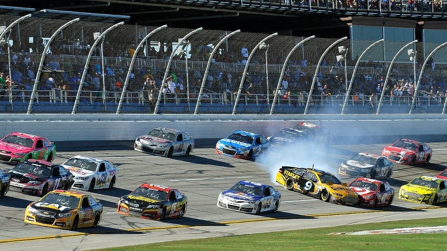 Sprint Cup Series driver Marcos Ambrose (9) slams into driver Juan Pablo Montoya (42) as a pack of cars race through the tri-oval in the NASCAR Sprint Cup Series auto race at the Talladega Superspeedway in Talladega, Ala., Sunday, Oct. 20, 2013. (AP Photo/Padriac Major)