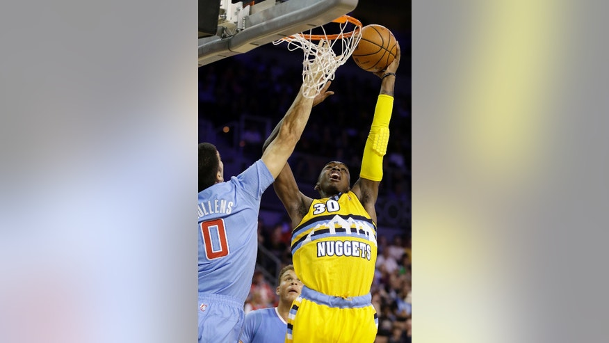 The Los Angeles Clippers' Byron Mullens covers a shot from the Denver Nuggets' Quincy Miller during the second half of a preseason NBA basketball game on Saturday, Oct. 19, 2013, in Las Vegas. The Clippers defeated the Nuggets in overtime 118-111. (AP Photo/Isaac Brekken)
