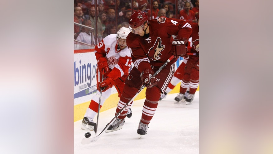 Phoenix Coyotes defenseman Zbynek Michalek (4) and Detroit Red Wings center Pavel Datsyuk (13) vie for the puck in the first period during an NHL hockey game Saturday, Oct. 19, 2013, in Glendale, Ariz. (AP Photo/Rick Scuteri)