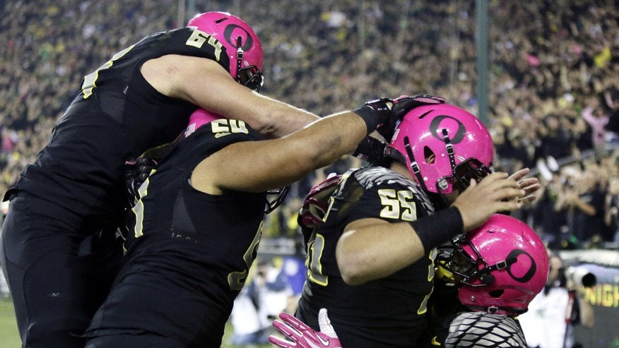 Oregon running back Byron Marshall, right, celebrates his touchdown with teammates, from left, Tyler Johnstone, Hamani Stevens and Hroniss Grasu during the first half of an NCAA college football game against Washington State in Eugene, Ore., Saturday, Oct. 19, 2013. (AP Photo/Don Ryan)