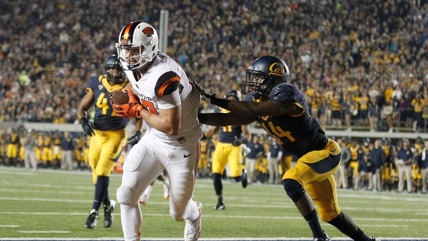 Oregon State tight end Caleb Smith (10) catches a touchdown pass in front of California cornerback Cameron Walker (14) during the first quarter of an NCAA college football game in Berkeley, Calif., Saturday, Oct. 19, 2013. (AP Photo/Tony Avelar)