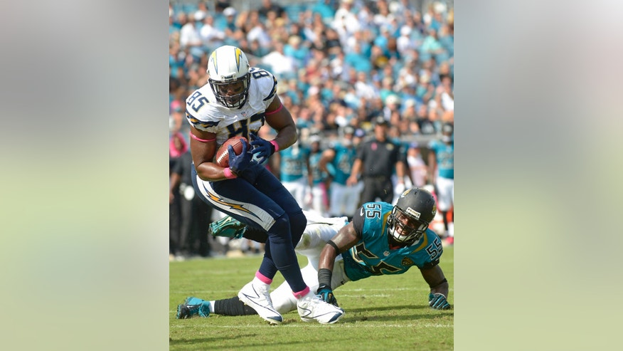 San Diego Chargers tight end Antonio Gates (85) runs the ball as Jacksonville Jaguars' Geno Hayes (55) defends during the second half of an NFL football game in Jacksonville, Fla., Sunday, Oct. 20, 2013. (AP Photo/Phelan M. Ebenhack)