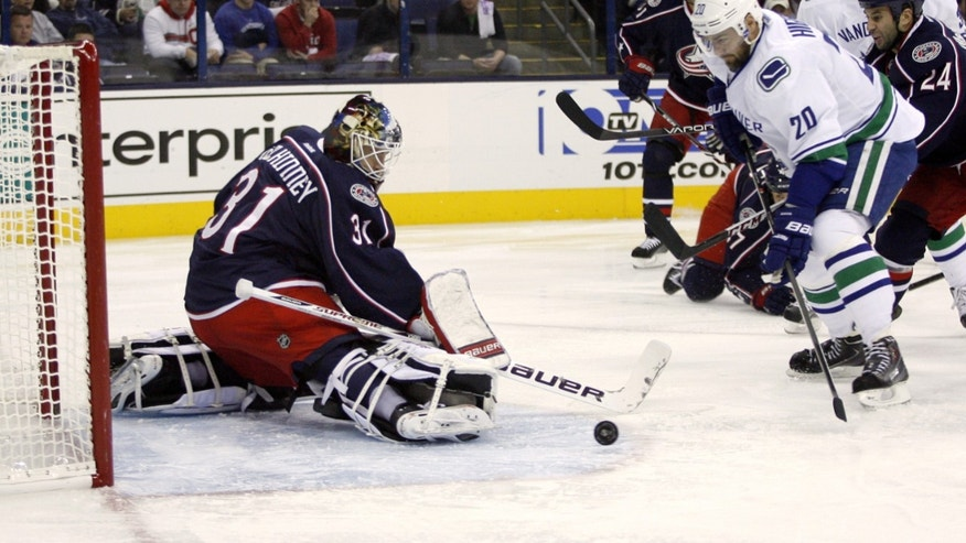 Columbus goalie Curtis McElhinney (31) blocks a shot by Vancouver's Chris Higgins (20) during the first period of an NHL hockey game Sunday, Oct. 20, 2013, in Columbus, Ohio. (AP Photo/Mike Munden)