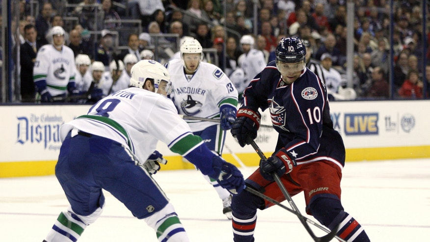 Columbus's Marian Gaborik (10), of Slovakia, shoots as Vancouver's Ryan Stanton, left, defends during the second period of an NHL hockey game Sunday, Oct. 20, 2013, in Columbus, Ohio. (AP Photo/Mike Munden)